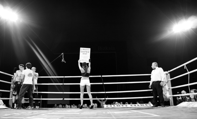 En el combate de boxeo la chica de round pasa el número de asalto