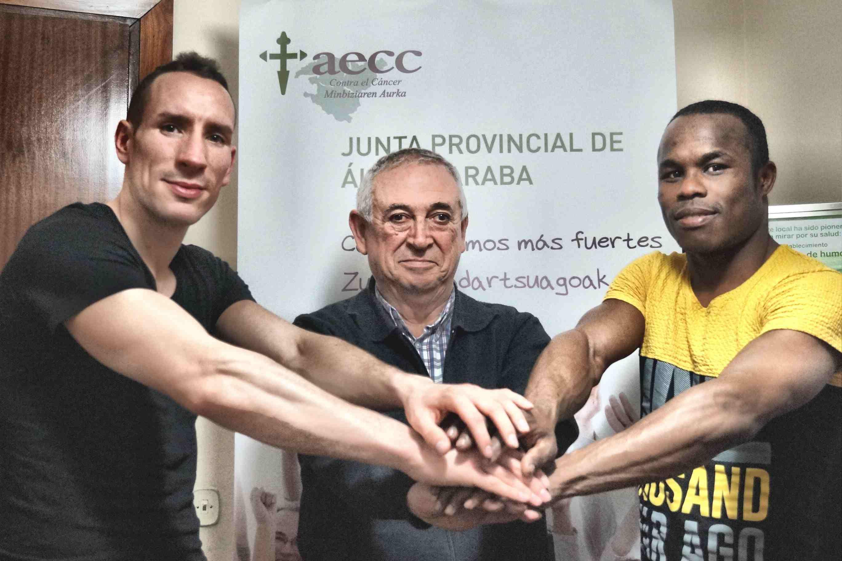 El luchador Sergio Sánchez, el señor Alfredo Ibisate, de la junta de la Asociación Contra el Cáncer de Vitoria-Gasteiz, y el boxeador nacho Mendoza
